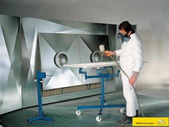 Bild zeigt einen Lackierer vor einer GESCHA Farbnebelabsaugwand Spritzwand Spritznebelabsauganlage. Die Anlage wird z.B. im Lackierraum, einem Spritzplatz oder Lackierkabine eingesetzt.